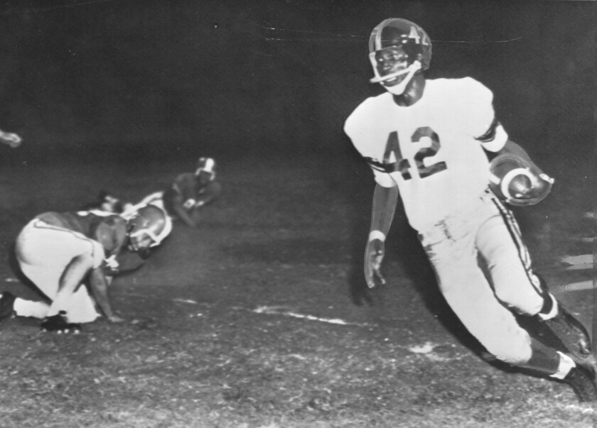 USC's C.R. Roberts (42) leaves University of Texas defenders behind during a 1956 game in Austin, Te