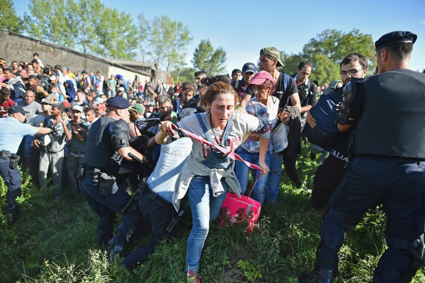 Migrants force their way through police lines at the Tovarnik, Croatia, station to board a train bound for Zagreb, Croatia, on Thursday.