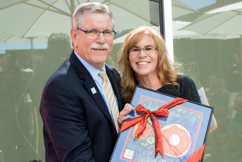 Ronald McDonald House Charities of San Diego president and CEO Chuck Day presents La Jolla resident Trulette Clayes pose with art made by a guest of Ronald McDonald House at the reopening of the Jospeh Clayes III Great Room.