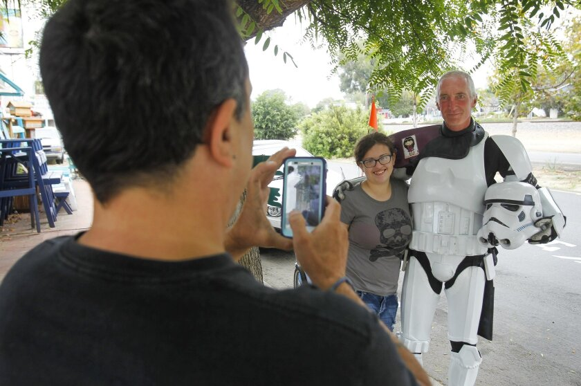 Kevin Doyle poses with Selena Flores, 15, as Selena's father Michael Flores takes a picture in Leucadia.