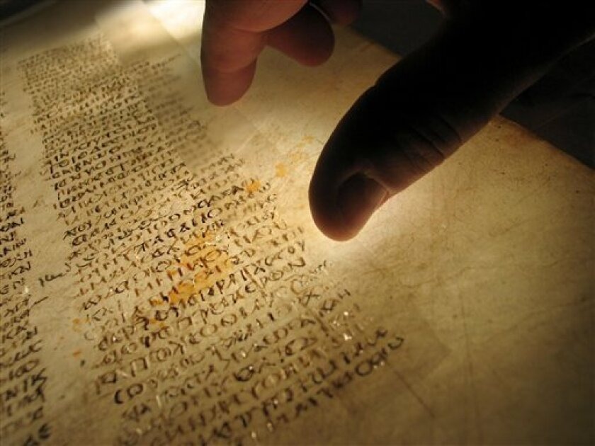 "This undated picture made available by the British Library shows a reader examining a page from the earliest surviving Christian Bible. The British Library says the surviving pages of the world's oldest Bible have been reunited _ digitally. The library says the early Christian work known as the Codex Sinaiticus had been housed in four separate locations across the world for more than 150 years. It became available Monday for perusal on the Web so scholars and others can get a closer look. The library says the work will allow scholars to further study the ""unique treasure."" The project united organizations from Great Britain, Germany, Russia and Egypt. Each possessed parts of the 1,600-year-old manuscript. They worked together to publish new research into the history of the Codex and transcribed 650,000 words during a four-year period. (AP Photo/The British Library)"