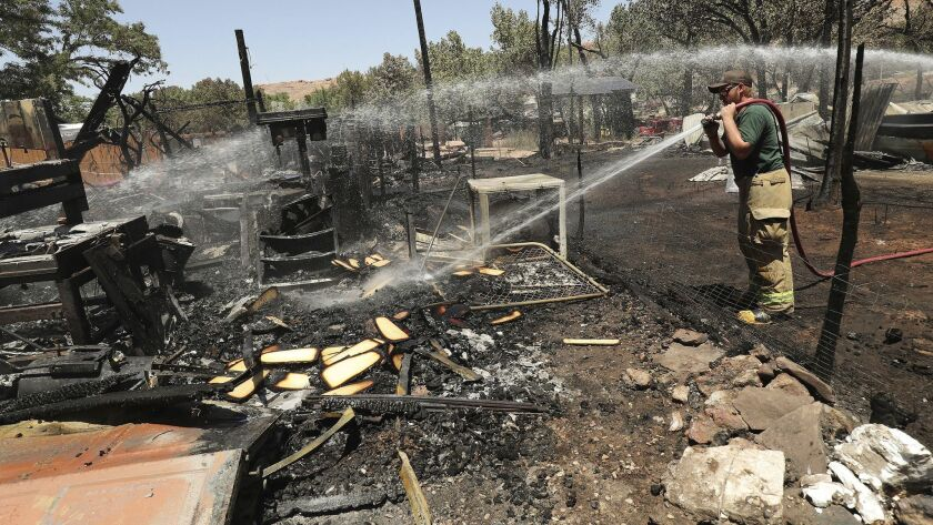 A firefighter douses embers at the site of a blaze in Moab, Utah, which destroyed eight homes.