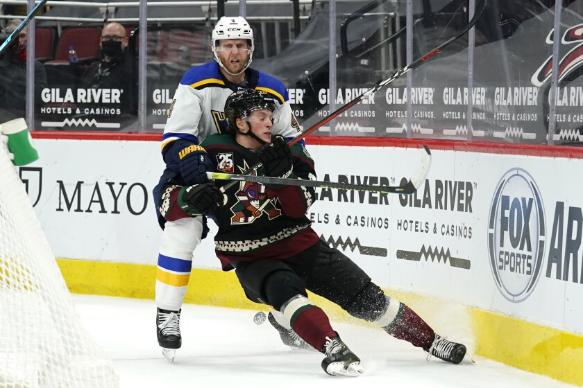 St. Louis Blues defenseman Carl Gunnarsson (4) shields Arizona Coyotes left wing Dryden Hunt from the puck in the second period during an NHL hockey game, Friday, Feb. 12, 2021, in Glendale, Ariz. (AP Photo/Rick Scuteri)