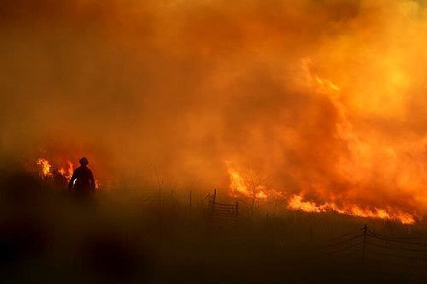 A Chula Vista city firefighter works the head of the Harris Fire as it rages in the hills above Eastlake.