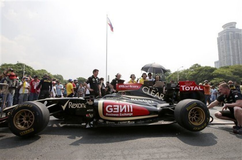 Lotus Formula One crew prepare their race car for the ceremony at Kilometer 0 in Manila, Philippines Saturday May 4, 2013. The Lotus Formula One team, with Filipino-Swiss driver Marlon Stockinger, is in Manila for the first time to promote and encourage Filipinos to patronize the sport. (AP Photo/Bullit Marquez)