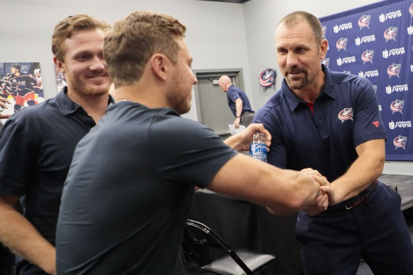 Columbus Blue Jackets new head coach Brad Larsen, right, greets player Cam Atkinson, left after an NHL hockey press conference on Friday, June 11, 2021 at Nationwide Arena in Columbus, Ohio. (Joshua A. Bickel/The Columbus Dispatch via AP)