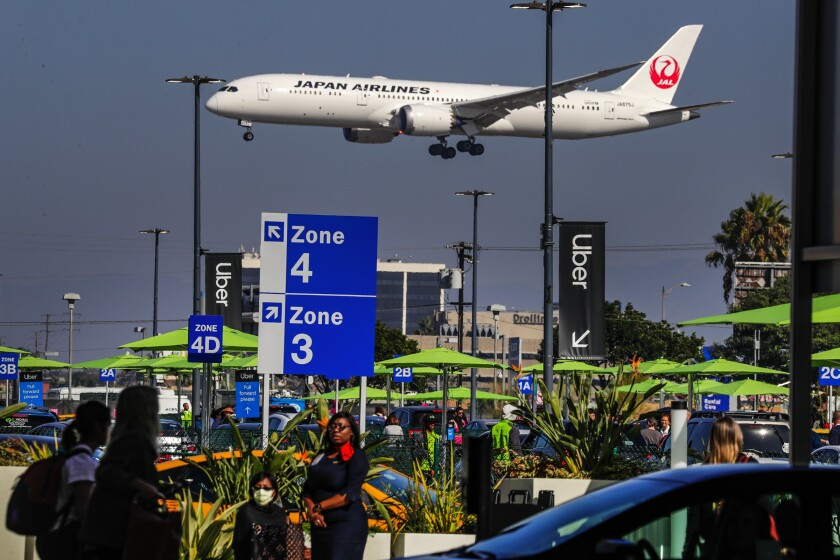 Travelers use the new LAXit lot as a Japan Airlines plane passes overhead.