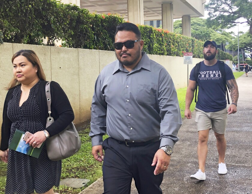 FILE - In this Sept. 25, 2019 file photo, former Honolulu police officer Reginald Ramones, center, walks down a street in Honolulu. Samuel Ingall, a homeless man, is suing the Honolulu Police Department and the city after he says officers forced him to lick a urinal in a public restroom. John Rabago, a police officer who remains on restricted duty, pleaded guilty in December to depriving Ingall of his civil rights. Ramones, who left the department in August, pleaded guilty to a lesser charge that he knew Rabago committed a civil rights violation but didn't inform authorities. (AP Photo/Jennifer Sinco Kelleher, File)