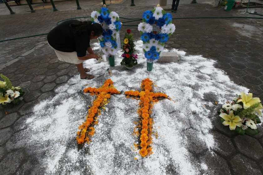 A woman makes a couple of crosses out of flowers at the exact place where a mob beat, killed and burned two pollsters who were conducting a survey, in front of the Municipal Palace in Ajalpan, Puebla, Mexico, Wednesday, October 21, 2015. Police had tried to protect the pollsters, Rey David Copado Molina, 39, and Jose Abraham Copado Molina, 32, but the mob dragged them from the jail, beat them, killed them and then burned their bodies. (AP Photo/Marco Ugarte)