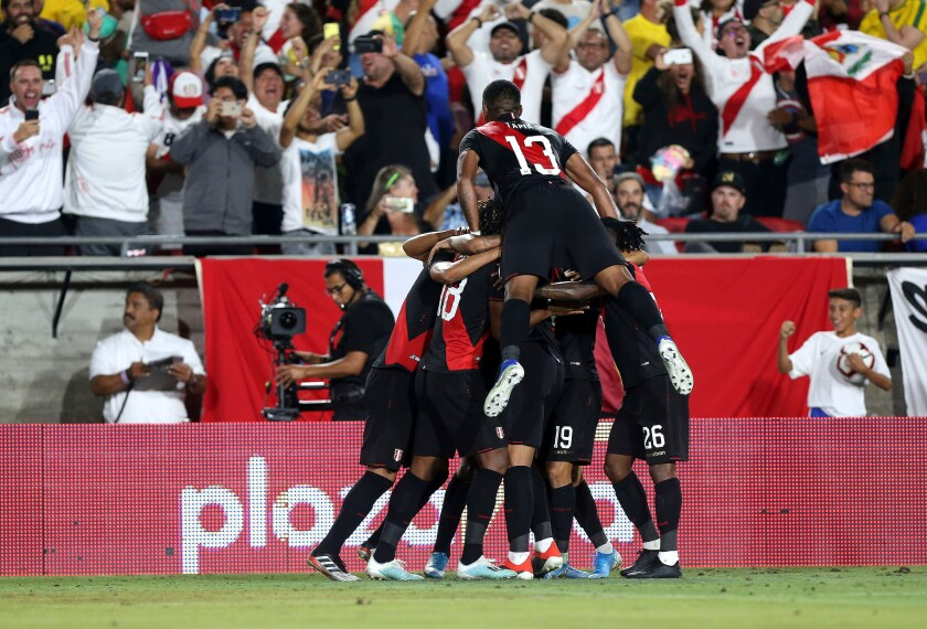 Peru celebrates after Luis Abram scores in the 85th minute of the second half during a friendly soccer match between Brazil and Peru at the Coliseum on Tuesday.