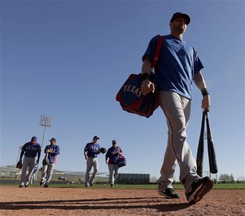 Players for the Texas Rangers walk to practice fields during a spring training baseball workout Saturday, Feb. 16, 2013, in Surprise, Ariz. (AP Photo/Charlie Riedel)
