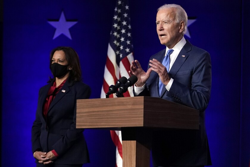 Joe Biden gestures with both hands as he speaks at a lectern with Kamala Harris, wearing a mask, standing nearby.