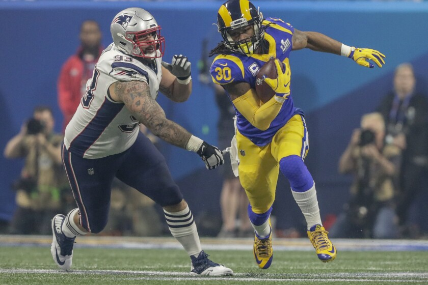 Rams running back Todd Gurley runs past a Patriots defensive lineman Larence Guy during Super Bowl LIII at Mercedes-Benz Stadium.