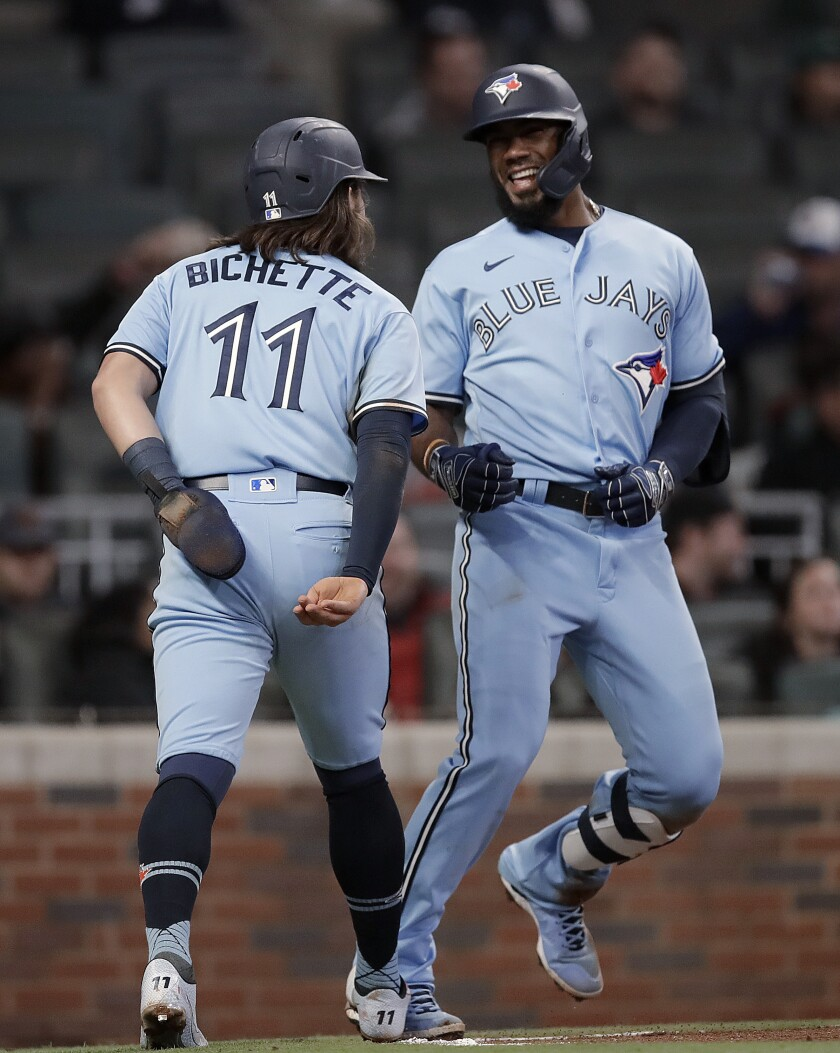 Toronto Blue Jays' Teoscar Hernandez, right, celebrates with Bo Bichette (11) after hitting a two-run home run against the Atlanta Braves during the ninth inning of a baseball game Wednesday, May 12, 2021, in Atlanta. (AP Photo/Ben Margot)
