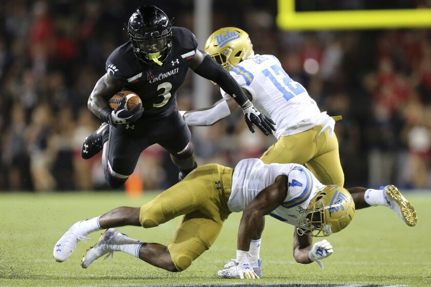 Cincinnati running back Michael Warren II, top left, is upended by UCLA defensive back Stephan Blaylock, bottom.