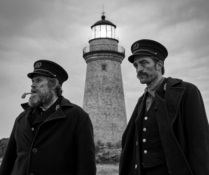 "Willem Dafoe and Robert Pattinson in the movie ""The Lighthouse,"" with the titular object behind them."