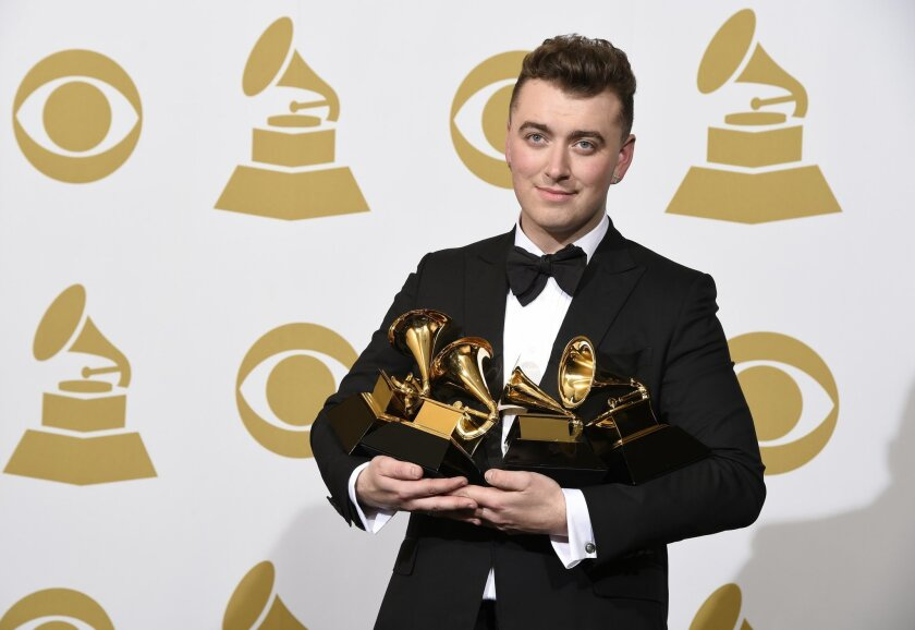 """Sam Smith poses in the press room with the awards for best new artist, best pop vocal album for """"In the Lonely Hour"""", song of the year for """"Stay With Me"""", and record of the year for """"Stay With Me"""" at the 57th annual Grammy Awards at the Staples Center on Sunday, Feb. 8, 2015, in Los Angeles. (Photo"""