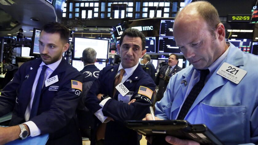 Specialists Matthew Greiner, left, and Peter Mazza, center, work with trader Peter Mancuso on the floor of the New York Stock Exchange.