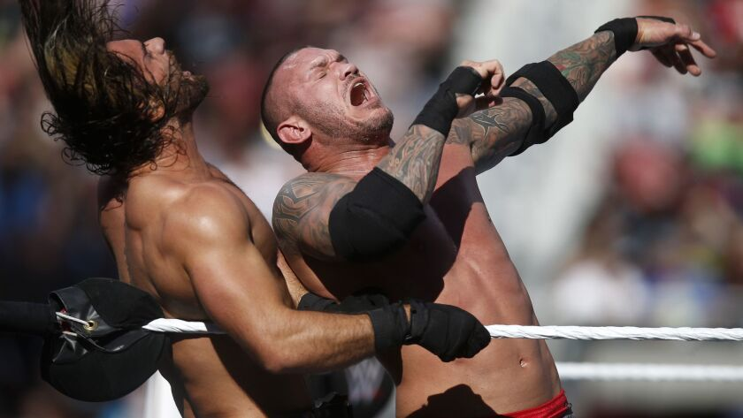 WWE's Seth Rollins, left, takes a hit from Randy Orton during WrestleMania at Levi's Stadium in Santa Clara, Calif., in 2015.