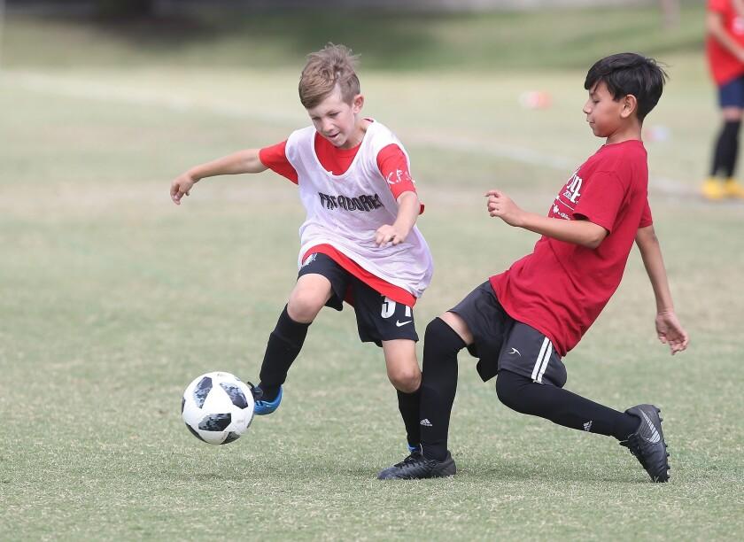 Kaiser's Cameron Deisner, left, battles, Romeo Flores of Costa Mesa Adams, in a boys' fifth and si