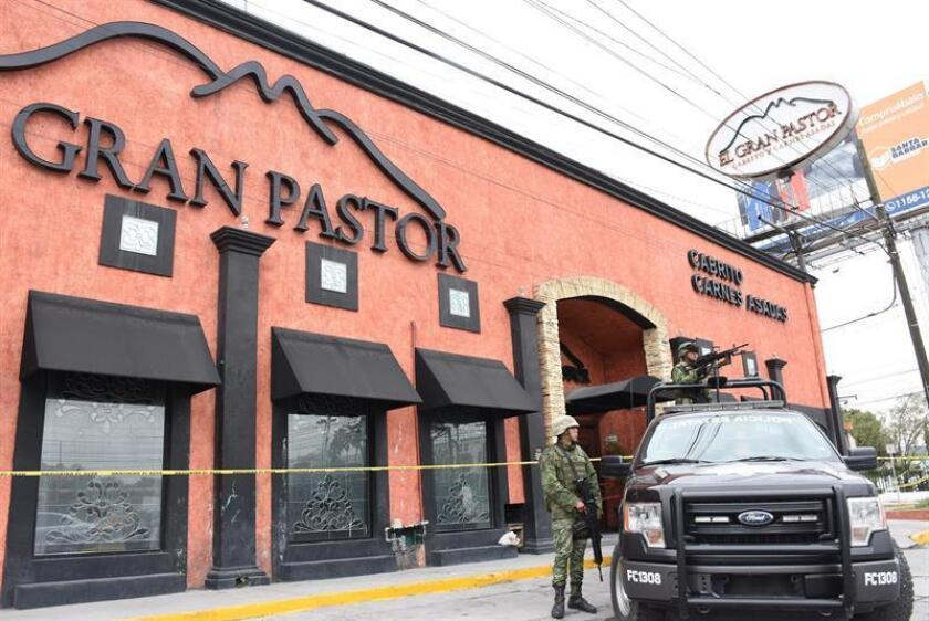Officers of the Mexican Army guard a restaurant on Feb. 8, 2019, in Monterrey, Mexico, where a group of armed and hooded men evacuated the employees of the restaurant El Gran Pastor, one of the best known of the Mexican city of Monterrey, sprayed gasoline inside and set fire to it, an attack that left two injured, informed the New Prosecutor's Office of Nuevo Leon. EPA-EFE / Juan Cedillo