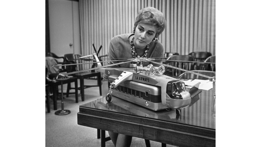 A model of a helicopter with a passenger-carrying pod is inspected by Ann Orbeck.