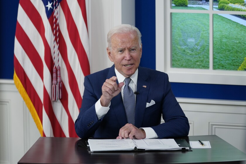 President Biden points as he speaks from a White House desk during a virtual summit.