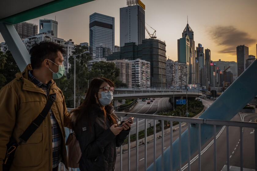 People wearing protective masks walk on a pedestrian bridge on Jan. 29 in Hong Kong.