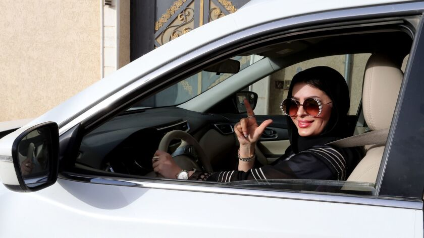 A motorist poses behind the wheel in Riyadh on June 24, the day Saudi Arabia's ban on women driving cars was lifted.