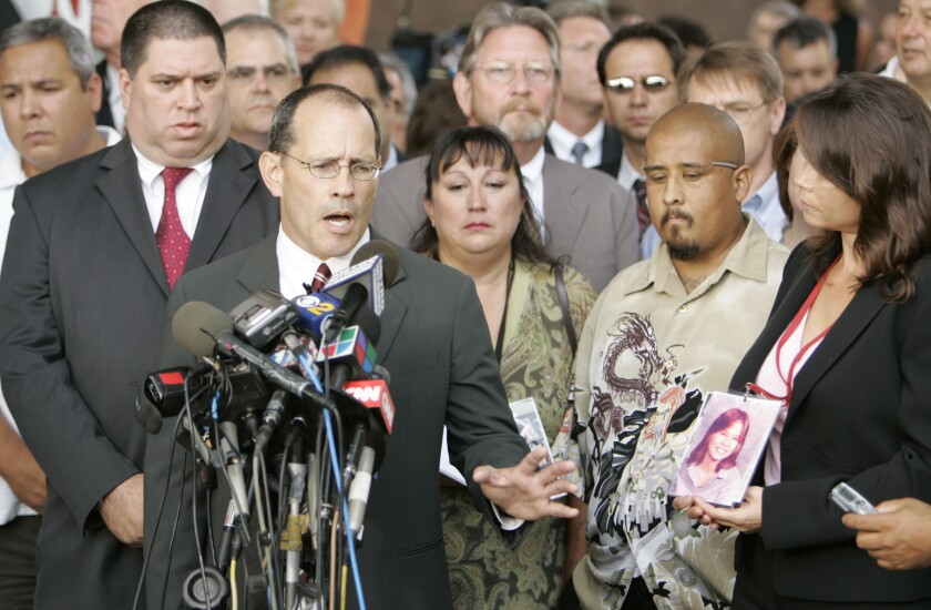 Attorney Ray Boucher is surrounded by plaintiffs as he addresses the media after the settlement.