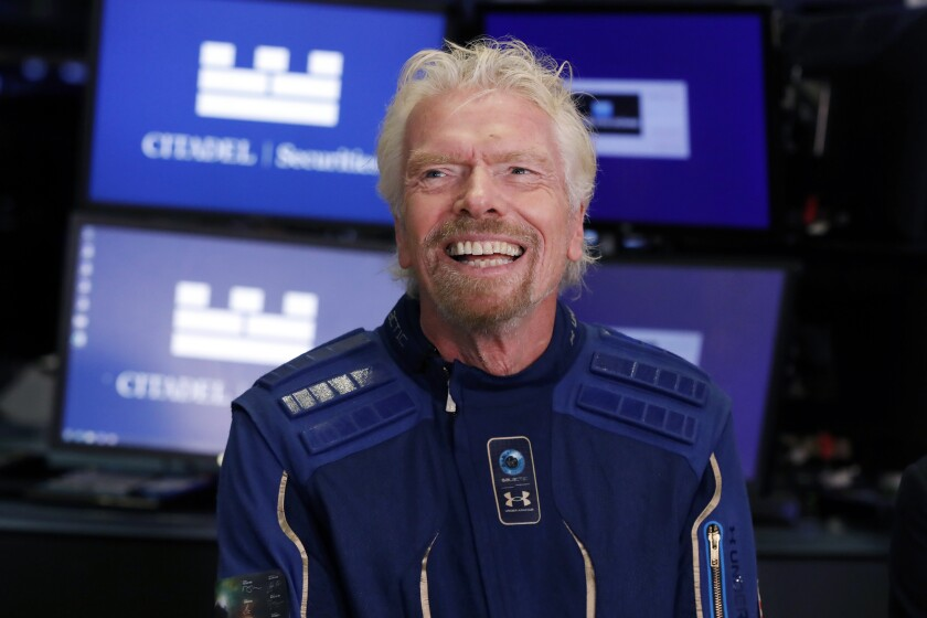 FILE - In this Monday, Oct. 28, 2019, file photo, Sir Richard Branson, founder of Virgin Galactic, is interviewed on the floor of the New York Stock Exchange. Branson said it was an honor and a once-in-a-lifetime experience to don a drum major's uniform and march ahead of a New Orleans high school band. But some of the Catholic school's fans apparently were less enthusiastic about Branson's appearance Thursday, Oct. 7, 2021, with the St. Augustine High School Marching 100, the band that integrated an exclusive Mardi Gras parade. (AP Photo/Richard Drew, File)