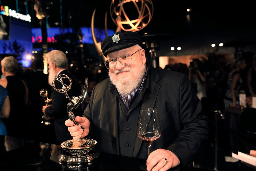 """Game of Thrones"" author George R.R. Martin holding an Emmy statue."