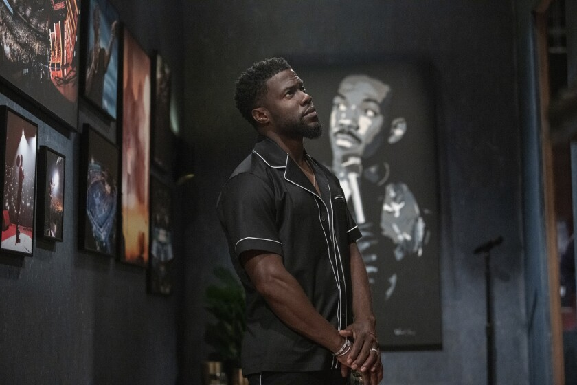 Kevin Hart stands amid portraits of comedy predecessors, including Eddie Murphy.