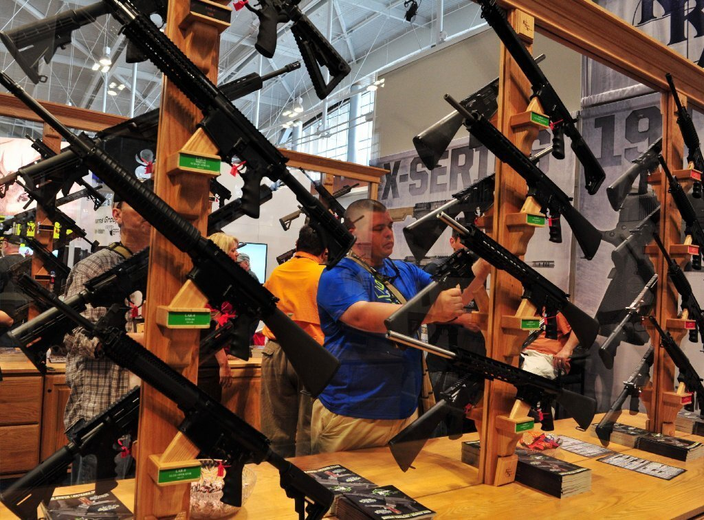 Convention attendees look at weapons on display at the 2015 NRA Annual Convention in Nashville, Tenn., on April 10, 2015. The annual NRA meeting and exhibit, expected to draw over 70,000 people.