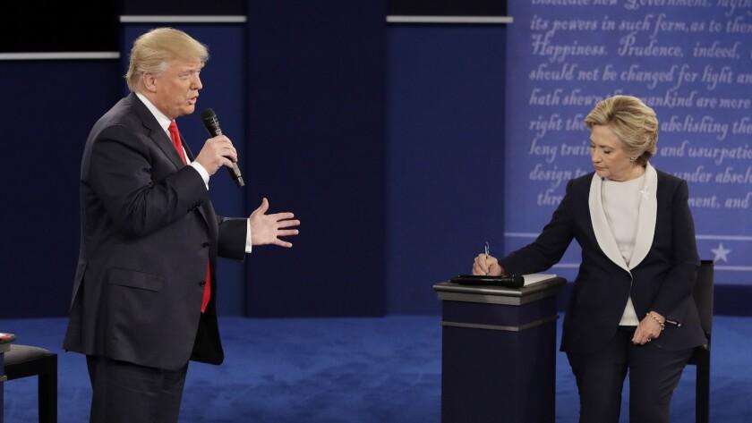 Republican presidential nominee Donald Trump speaks while Democratic presidential nominee Hillary Clinton takes notes.