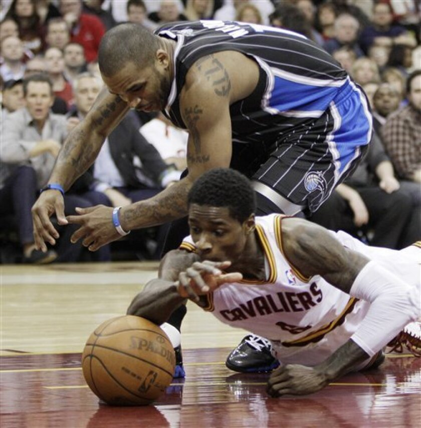 Orlando Magic's Jameer Nelson, top, and Cleveland Cavaliers' Manny Harris battle for a loose ball in the second quarter in an NBA basketball game, Monday, March 21, 2011, in Cleveland. (AP Photo/Tony Dejak)