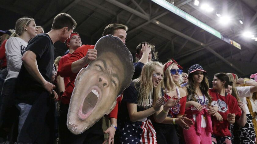A fan holds a photo cutout of Gonzaga forward Rui Hachimura during the first half of an NCAA college