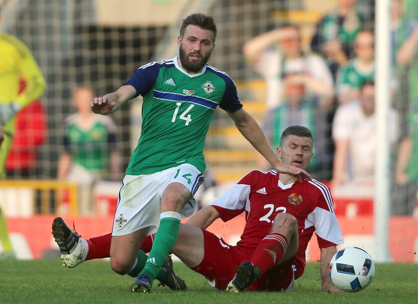 Northern Ireland's Stuart Dallas, left, and Belarus' Nikolai Yanush in action during the international friendly soccer match Northern Ireland against Belarus at Windsor Park, Belfast, Northern Ireland, Friday May 27, 2016. (Niall Carson  / PA via AP) UNITED KINGDOM OUT - NO SALES - NO ARCHIVES