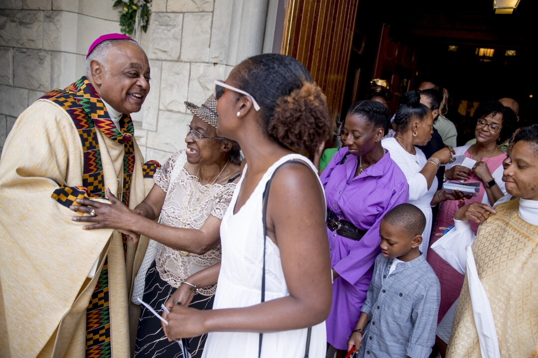 Archbishop Wilton Gregory, left, greets parishioners at St. Augustine Catholic Church in Washington, D.C.