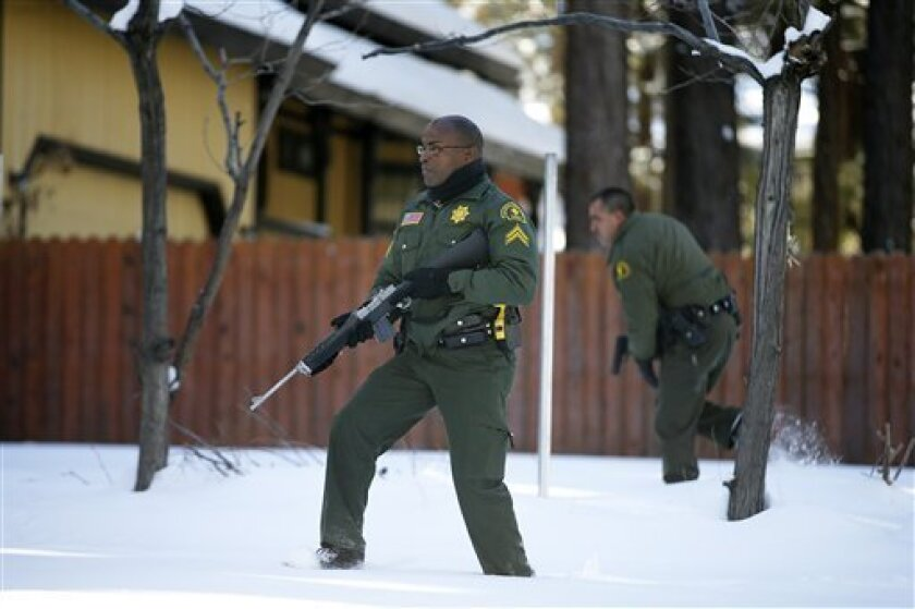 San Bernardino County Sheriff's officers Ken Owens, center, and Bernabe Ortiz search a home for former Los Angeles police officer Christopher Dorner in Big Bear Lake, Calif, Sunday, Feb. 10, 2013. The hunt for the former Los Angeles police officer suspected in three killings entered a fourth day in