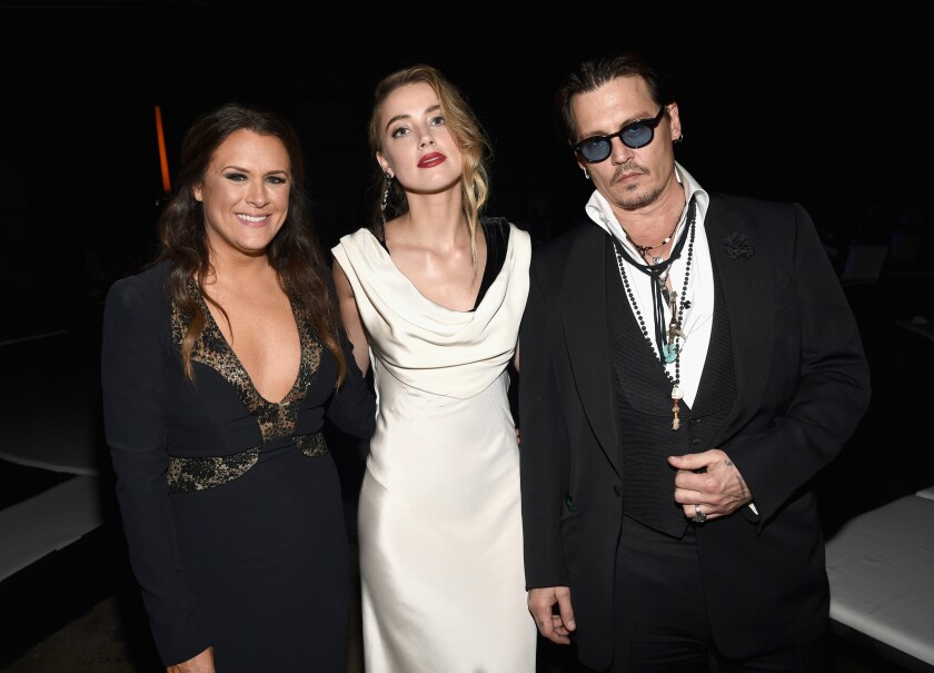 Art of Elysium founder Jennifer Howell, left, with honoree Amber Heard and Johnny Depp at the organization's gala Jan. 10.