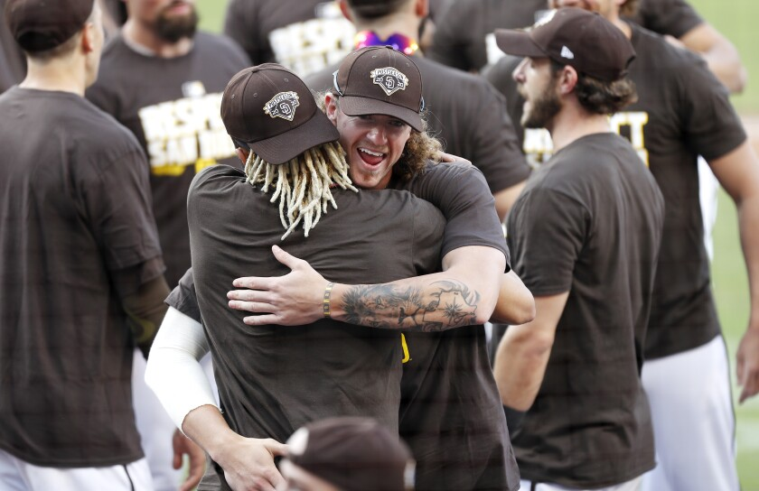 Chris Paddack and Fernando Tatis Jr. celebrate after Padres beat the Mariners on Sunday to clinch a spot in the playoffs.