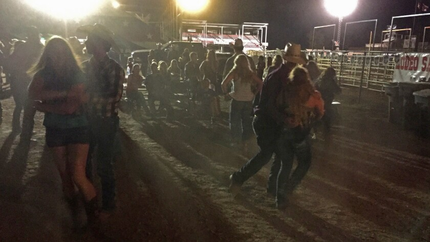 At the end of a rodeo night in Belle Fourche, S.D., young cowboys and cowgirls dance in the darkness and dust.