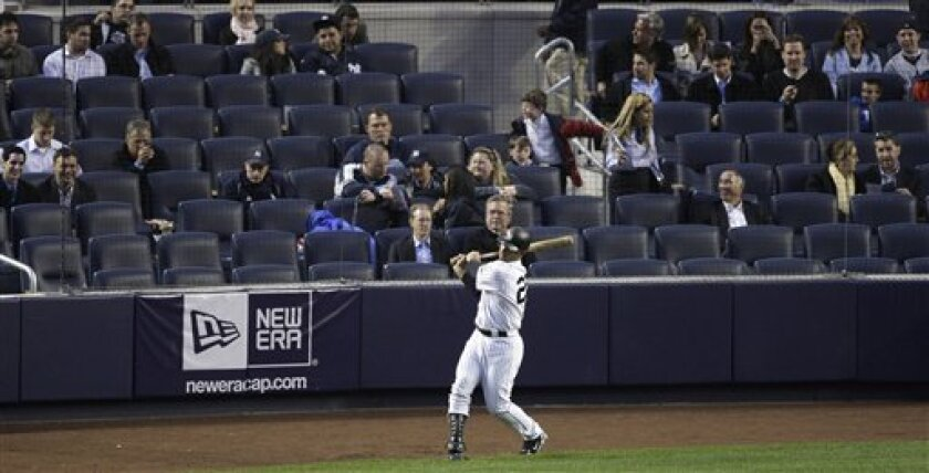 FILE - In this April 30, 2009, file photo, New York Yankees' Jorge Posada warms up on deck as fans in the Legends seats watch the first inning of the Yankees' baseball game against the Los Angeles Angels at Yankee Stadium in New York. Yankees chief operating officer Lonn Trost said no changes were planned to the policy preventing fans with tickets in other parts of the stadium from getting close to the field during batting practice. Seats in the first nine rows, called the Legends Suite, cost $500 to $2,625 and come with access to three restaurants and lounges. The area is separated from the rest of the lower deck by a concrete moat. (AP Photo/Julie Jacobson, File)