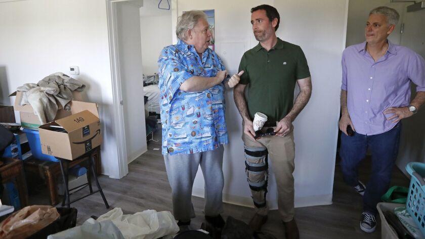 Navy veteran Glen Lipton, 67, left, talks to Kyle Paine, Community Development Partners president, c