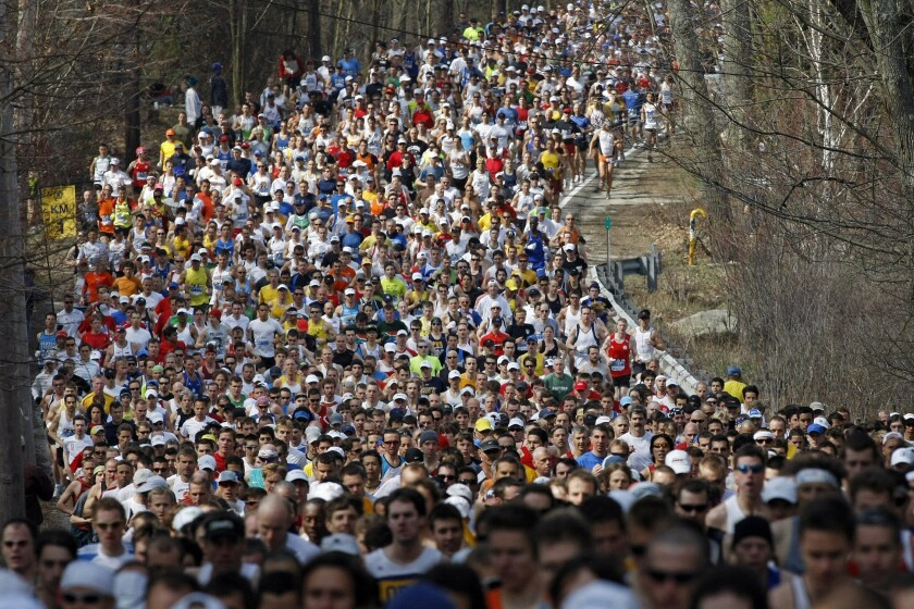 Runners round a curve and climb a hill during the first mile of the 2008 Boston Marathon.