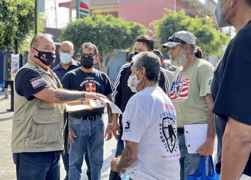 Robert Vivar (left) talking to a group of deported veterans
