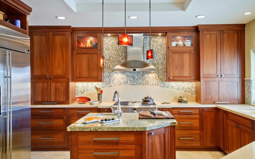 Cabinets in this kitchen remodeling project were designed with display areas to highlight a rotating collection of pottery designed by the homeowner's mother. Lights above the island match those above the bar.