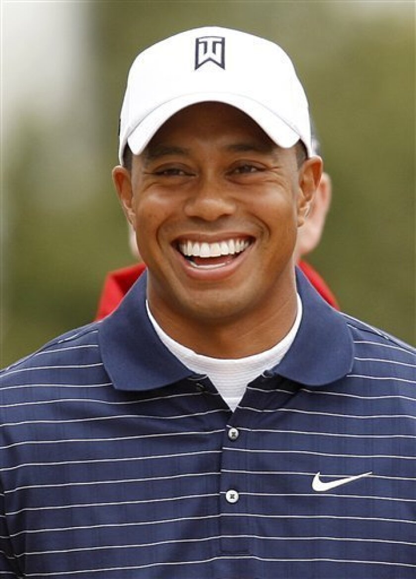 Tiger Woods from the US smiles as he arrives for a practice round for the British Open Golf Championship at Turnberry Golf Course, Turnberry, Scotland, Sunday, July, 12, 2009. (AP Photo/Peter Morrison)