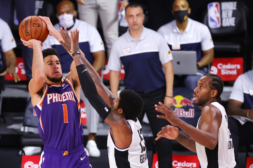 Phoenix Suns guard Devin Booker, left, shoots over Clippers forwards Paul George, center, and Kawhi Leonard at the buzzer.